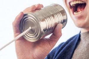 persona hablando a través de una lata con un hilo
